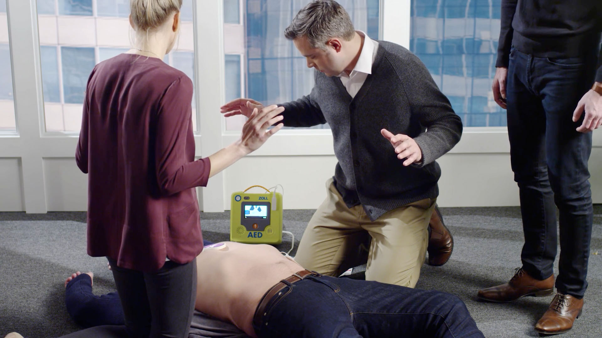 Co-workers standing over an employee who is experiencing cardiac arrest