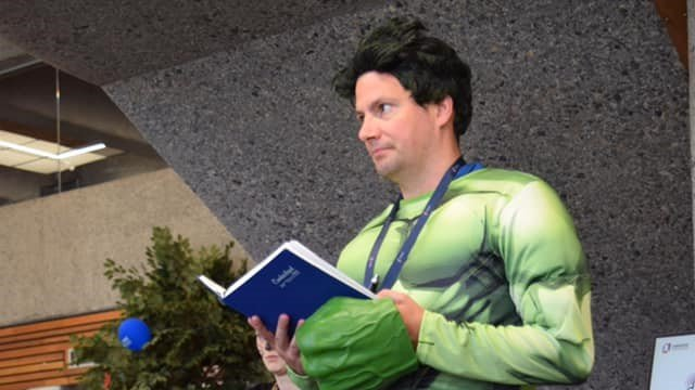 Man reading a book in an Incredible Hulk costume.