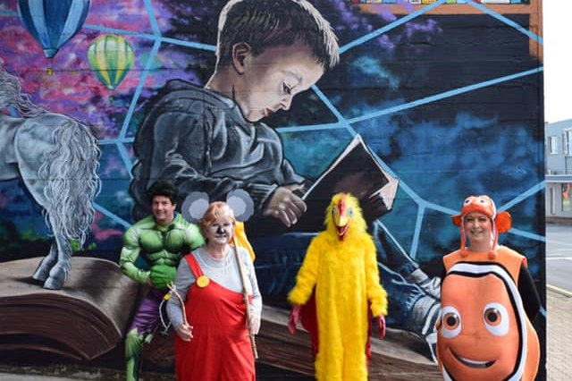 Adults dressed up as various characters including the incredible hulk in front of a mural of a child reading a book